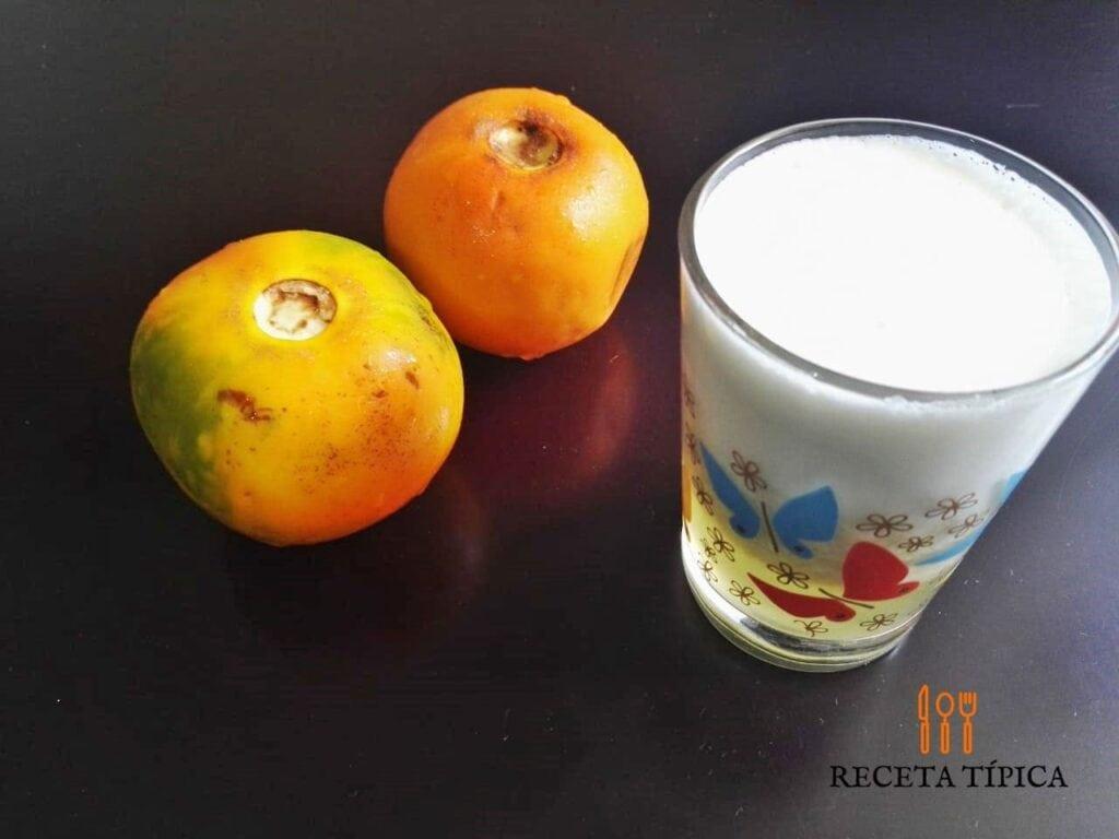 vaso con jugo de lulo y dos lulos en fruta