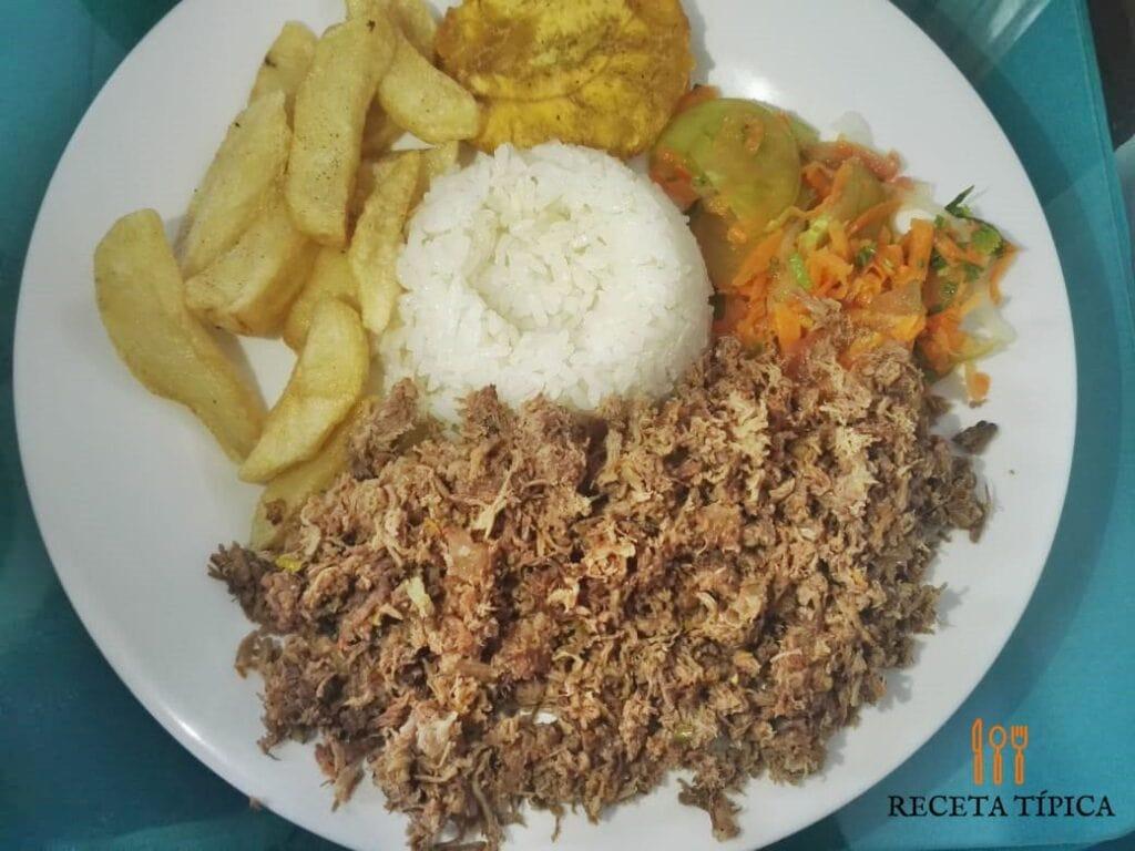 Plato con carne desmechada, patacones, papas fritas y ensalada