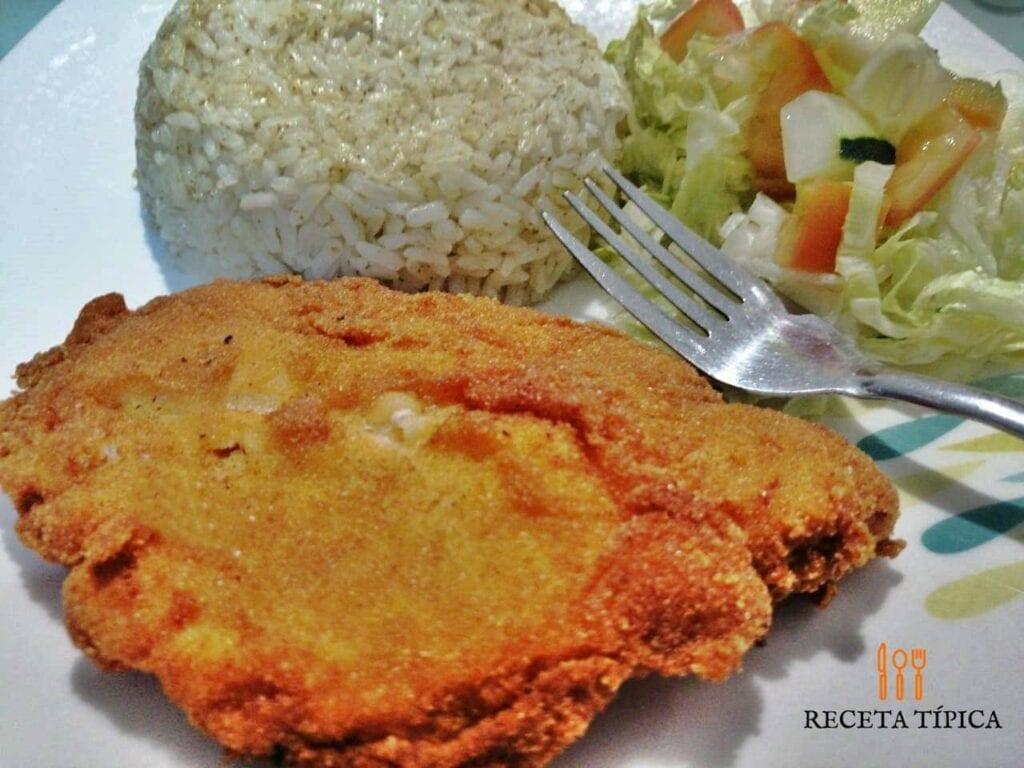 Plato con arroz, ensalada y milanesa de pollo al horno