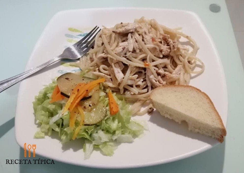 plato con Espagueti con pollo, ensalada y rodaja de pan