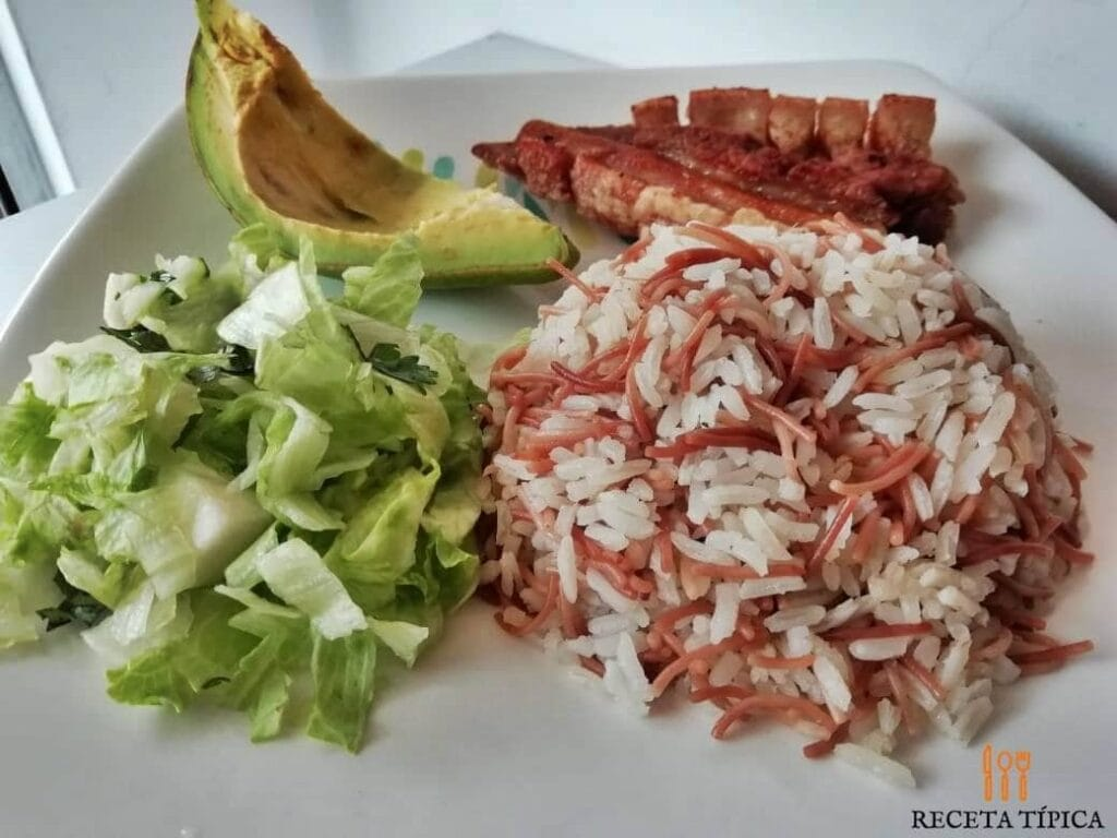 arroz con fideos, ensalada, aguacate y chicarrón