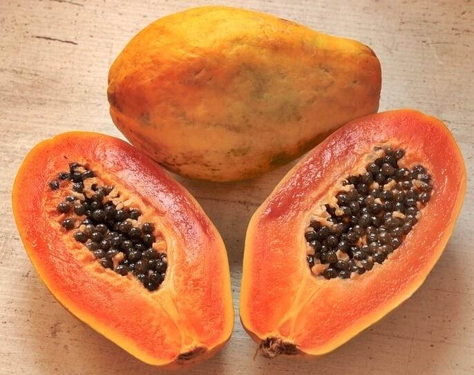 Una papaya entera y una papaya a la mitad