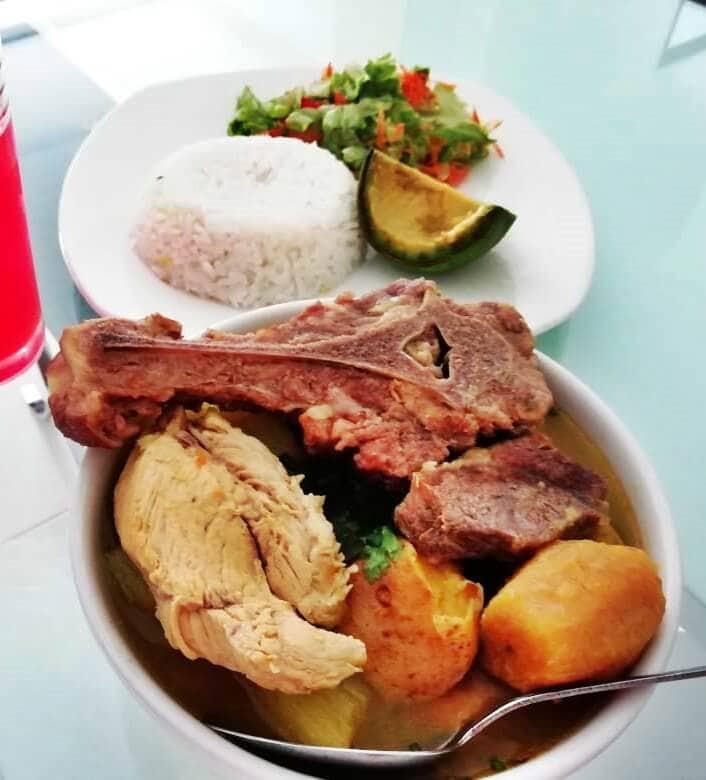 plato con sancocho trifásico, con arroz, ensalada y aguacate