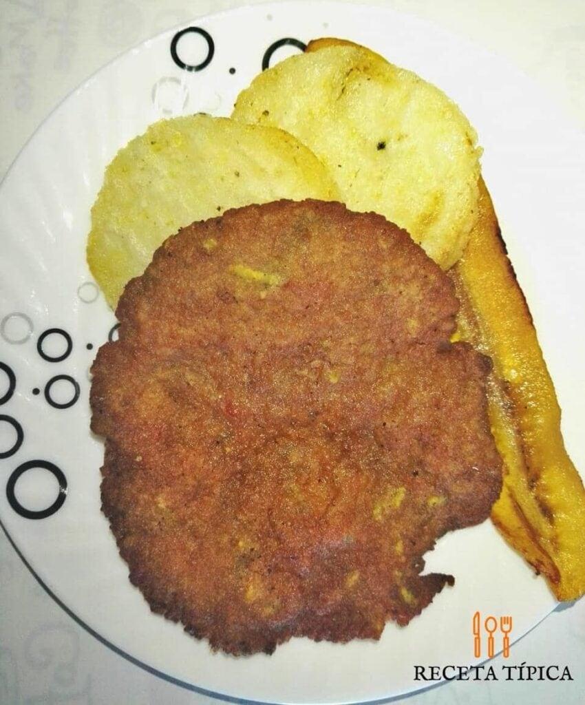 Plato con tortitas de carne acompañadas de arepas y tajadas.