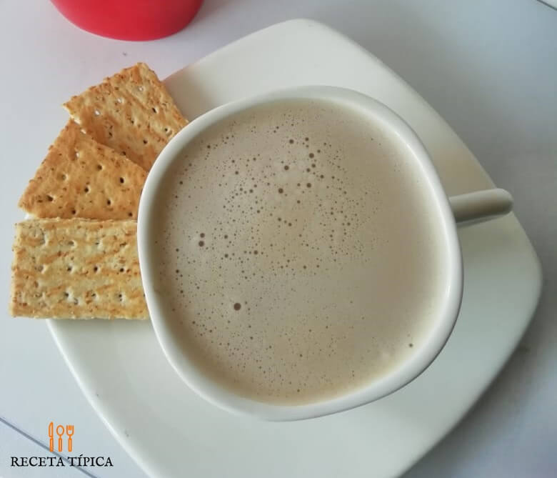 taza con café capuchino y galletas