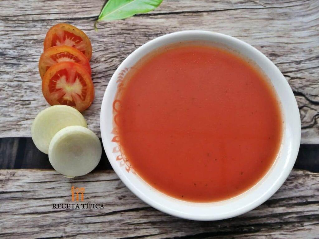 Plato con sopa de tomate, rodajas de tomate y cebolla